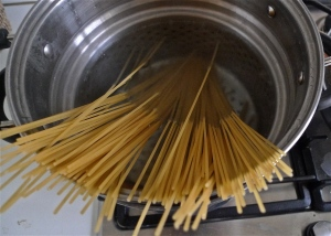 Spaghetti dropped into large pasta pot