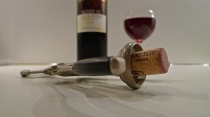 Opener w/ cork staged in front of bottle and wine glass