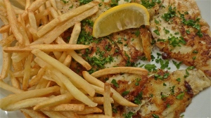 Plated Flounder fillets topped w parsley and surrounded by shoestring French fries/chips